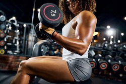African American female athlete with a pair of dumbbells in her hands performing the seated bicep curl