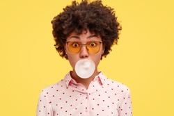 African American female blows bubble from chewing gum, has amazed expression, dressed in fashionable clothes and shades, isolated over yellow background. Lovely dark skinned woman poses indoor