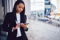African American female entrepreneur in corporate suit using online banking for transferring money distantly via smartphone. Confident businesswoman texting email letter on cellphone using internet