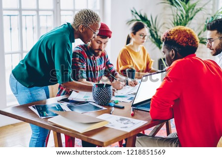 African american female leader checking work of crew helping with making planning accountings,  coach of crew training employees during workshop, colleagues cooperating and helping  each other