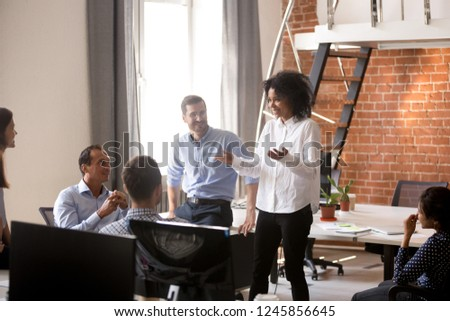 African American female leader, coach, trainer talking with motivated subordinates, team of office workers at company meeting, brainstorm, discussing business strategy, ideas, team building activity