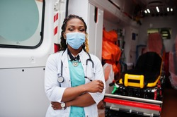 African american female paramedic in face protective medical mask standing in front of ambulance car.