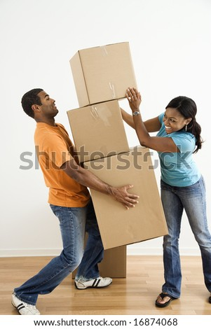 African American female placing boxes on large stack man is holding. - stock photo