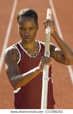 African American female pole vaulter holding pole