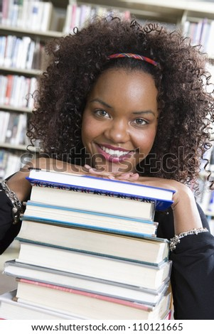 African American female student leaning on stack of books in library
