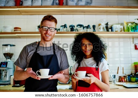 African American female with Afro hairdo and red haired male in eyeglasses employees of cafe in aprons with cups of coffee in hands looking at camera