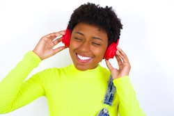 African American female with curly bushy wears jeans overalls over white wall smiles broadly feels very glad listens favourite music track via wireless headphones closes eyes.