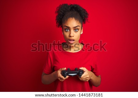 African american gamer woman playing video game using joystick over isolated red background scared in shock with a surprise face, afraid and excited with fear expression