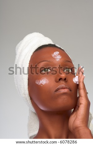 African-American girl applying facial skincare product (gray background)