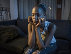 African American girl at night suffering depression - young attractive sad and depressed black woman lying thoughtful feeling sick on sofa couch in pain and worry