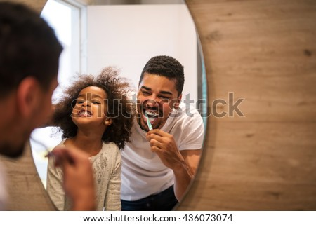 African american girl brushing teeth with dad.