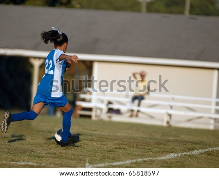 African American girl chases the soccer ball
