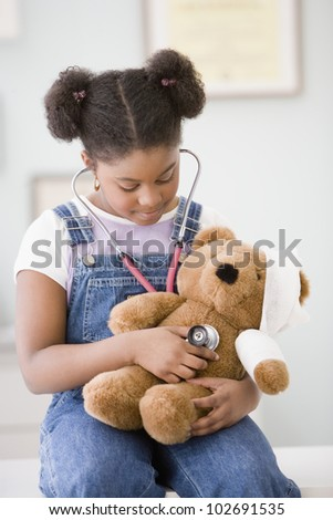 African American girl holding stethoscope on teddy bear
