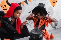 african american girl in halloween costume gesturing near witch cauldron with potion and brother with toy spider