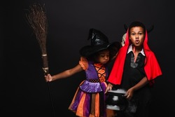 african american girl in halloween costume holding broom and blowing on cauldron with potion near brother isolated on black