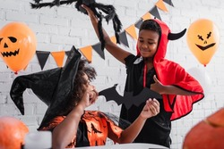 african american girl in halloween costume holding paper cut bat near happy brother with toy spider showing thumb up