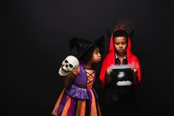 african american girl in halloween costume holding skull and blowing on witch cauldron with potion near brother isolated on black