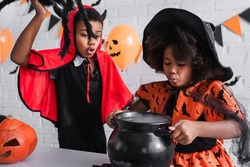 african american girl in halloween costume holding witch cauldron with potion near brother with toy spider