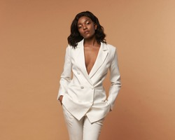 African american girl in white suit with wavy hair and make-up posing on a beige background. Fashion style full length studio portrait. Elegant fashionable woman