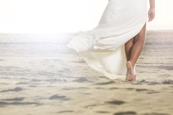 African American girl is walking on the sand with a flowing white dress.