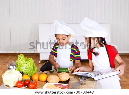 African american girl looks at her brother cutting cucumber