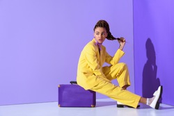 african american girl posing in yellow suit sitting on purple suitcase, on trendy ultra violet background