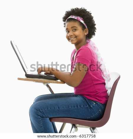 African American girl sitting in school desk typing on laptop computer smiling at viewer.
