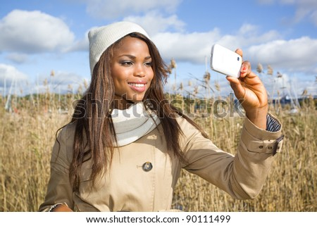 African american girl taking pictures with cellphone - stock photo