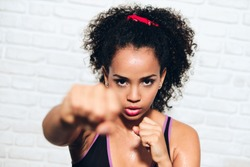 African american girl training in fitness club, gym, doing sport activity. Pretty young woman working out, fighting, boxing, exercising for self-defense