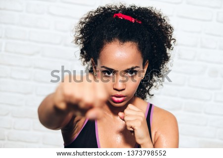 African american girl training in fitness club, gym, doing sport activity. Pretty young woman working out, fighting, boxing, exercising for self-defense Stock photo ©