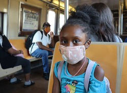 African American Girl wearing mask sitting in subway car