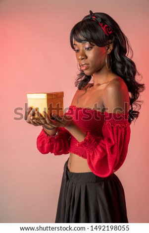 African American girl with a gold box in upturned hands