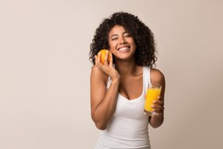 African-american girl with orange and glass of juice over light background