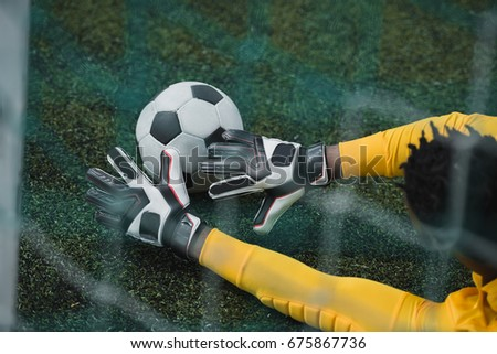 african american goalkeeper catching soccer ball during game