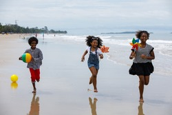 African American,group of children kids brother or sister hold hands and run together to play in the sea on summer vacation with family or school friend