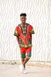 African American guy in national clothes on a background of a white wall