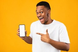 African American Guy Showing Smartphone Empty Screen Recommending Mobile Application Smiling To Camera Over Yellow Studio Background. Mockup