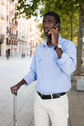 African american guy traveler talking on phone while walking with luggage along city street