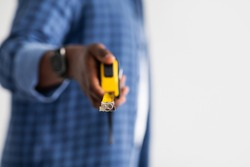 African american handyman holding measuring tape, isolated on white background with copy space, crop, closeup. Carpenter, construction with tape-line and engineer size measuring for repair.