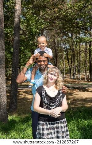 African American happy family: black father, mom and baby boy on nature. Use it for a child, parenting or love concept