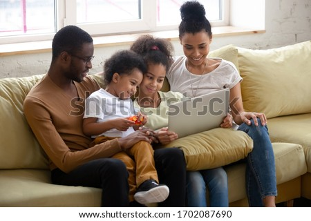 African american happy family with two children having good time using laptop. Young diverse smiling husband and wife with cute daughter and son sitting on couch at home looking at computer. stock photo