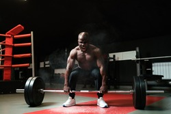 African American heavyweight man doing barbell squats. The powerlifting coach screams and lifts the barbell in the smoke. Smoke from talcum powder in the gym