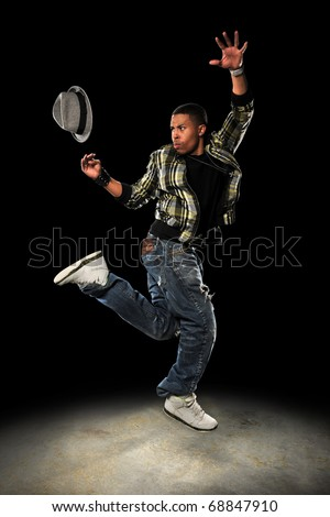 African American hip hop dancer performing with hat over dark background with spotlight