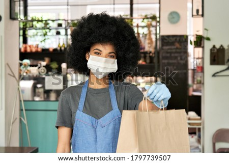 African American hipster waitress wearing face mask and gloves holding takeaway food order in hands giving bag standing in cafe. Coffee shop worker offering takeout safe restaurant take away delivery
