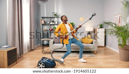 African American joyful happy handsome young guy vacuuming living room at home doing housework dancing having fun pretending to play on guitar, male cleaning house using vacuum, housework concept