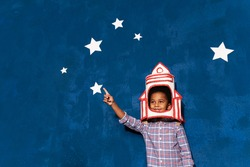 African american kid boy with rocket helmet on head on blue studio background with white stars. Portrait of smiling afro child playing in astronaut. Imagination and childish dream about cosmic space.