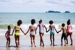 African American, Kids group in swimwear enjoying running to play the waves on beach. Ethnically diverse concept. Having fun after unlocking down from COVID 19. Summer holidays on beach with friends