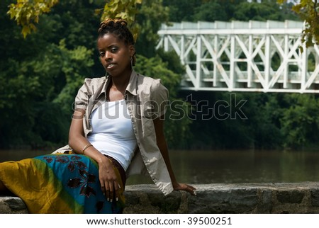 African American lady by water an bridge