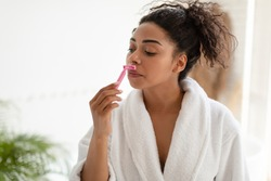 African American Lady Shaving Upper Lip Hair Removing Natural Moustaches With Safety Razor Standing In Bathroom At Home. Depilation Routine And Facial Hair Removal Concept