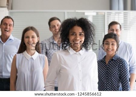 African American leader, coach posing, standing with multiracial group of employees in office, diverse happy group team staff members at background, successful business owner, look at camera